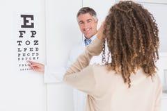 Vrouw die oogtest met optometrist doen stock foto's