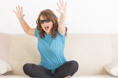 Vrouw die op 3D TV in glazen letten Stock Afbeeldingen