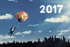 Vrouw die op ballons met 2017 vliegen Stock Afbeelding