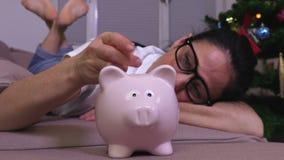 Vrouw die op bank en gezette muntstukken in spaarvarken liggen stock videobeelden