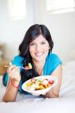 Vrouw die op bed eet royalty-vrije stock fotografie