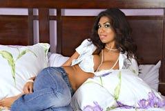 Vrouw die op bed legt Stock Foto's