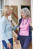 Vrouw die op Bejaarde Vrouwelijke Buur controleren stock afbeelding
