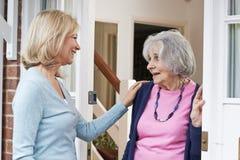 Vrouw die op Bejaarde Vrouwelijke Buur controleren stock fotografie