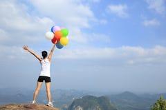Vrouw die op bergpiek toejuichen met kleurrijke ballons Stock Foto