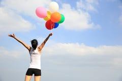 Vrouw die op bergpiek toejuichen met kleurrijke ballons Royalty-vrije Stock Afbeeldingen