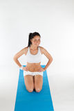 Vrouw die op blauw yogatapijt uitoefent Royalty-vrije Stock Fotografie