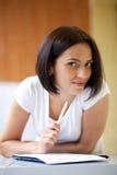 Vrouw die op blocnote schrijft om lijst thuis te doen Royalty-vrije Stock Foto's