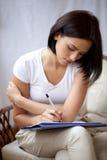 Vrouw die op blocnote schrijft om lijst thuis te doen Stock Fotografie
