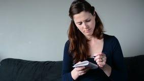 Vrouw die op blocnote schrijven om lijst te doen stock footage