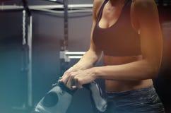 Vrouw die op bokshandschoenen voor trainingzitting bij de gymnastiek zetten Toont atletische lichaamsbouw in sportenbustehouder royalty-vrije stock foto's