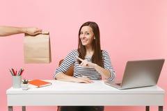 Vrouw die op bruine duidelijke lege lege die ambachtdocument zak, werk op kantoor met laptop richten op roze achtergrond wordt he royalty-vrije stock fotografie