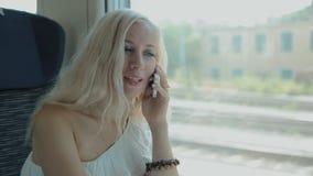 Vrouw die op celtelefoon spreken in de trein stock videobeelden