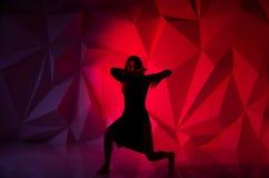 Vrouw die op de achtergrond van een mooie multicolored muur dansen Sexy slank eenzaam meisje met lang zwart haar in a royalty-vrije stock afbeelding