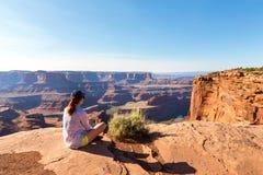 Vrouw die op de bovenkant van rotsachtige berg situeren stock afbeeldingen