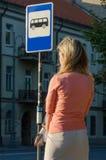 Vrouw die op de bus wacht Stock Foto's