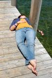 Vrouw die op de docklakeoever van het meer liggen Royalty-vrije Stock Foto's