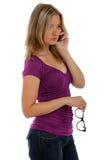 Vrouw die op de glazen van een telefoonholding spreekt Stock Foto's