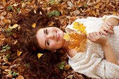 Vrouw die op de herfstbladeren liggen, openluchtportret royalty-vrije stock foto's