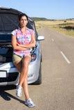 Vrouw die op de hulp van de autodienst in roadhelp in weg wachten Stock Afbeeldingen