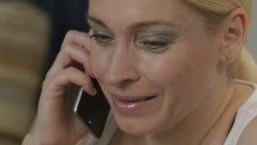 Vrouw die op de laag met een computertablet liggen en op de telefoon spreken stock footage