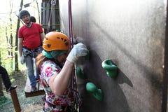 Vrouw die op de muur beklimmen stock afbeelding