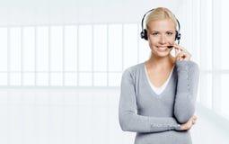 Vrouw die op de oortelefoon in bureau spreken Stock Afbeeldingen