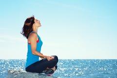 Vrouw die op de overzeese kust mediteren stock fotografie