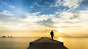 Vrouw die op de pijler in het overzees bij zonsondergang lopen Stock Foto's