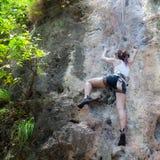 Vrouw die op de rots beklimmen Stock Foto's