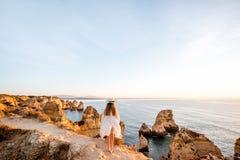 Vrouw die op de rotsachtige kustlijn in Lagos, Portugal reizen royalty-vrije stock fotografie