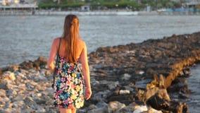 Vrouw die op de rotsen met de zomerachtergrond lopen stock video