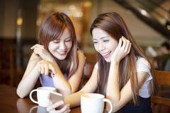 Vrouw die op de slimme telefoon in koffiewinkel letten Royalty-vrije Stock Afbeelding