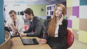 Vrouw die op de telefoon en de lach op het kantoor spreken stock footage