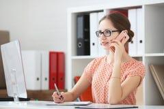 Vrouw die op de telefoon in het bureau spreken Royalty-vrije Stock Afbeeldingen