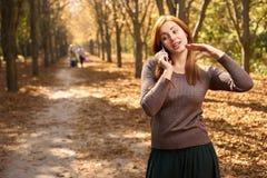 Vrouw die op de telefoon in het de herfstpark spreken Stock Afbeelding