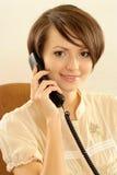 Vrouw die op de telefoon op een beige spreekt Royalty-vrije Stock Foto
