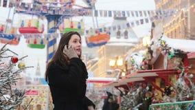 Vrouw die op de telefoon spreken die in de winter zich op de Kerstmismarkt bevinden op het Rode Vierkant in Moskou, Rusland stock footage