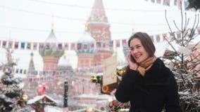 Vrouw die op de telefoon spreken die zich in de winter op het Rode Vierkant in Moskou, voor St Basil Cathedral bevinden stock video