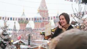 Vrouw die op de telefoon spreken die zich in de winter op het Rode Vierkant in Moskou, voor St Basil Cathedral bevinden stock videobeelden
