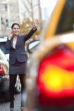 Vrouw die op de Telefoon van de Cel een Gele Cabine van de Taxi begroet Royalty-vrije Stock Afbeeldingen