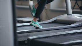 Vrouw die op de tredmolen in de gymnastiek lopen stock footage