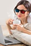Vrouw die op de vloer voor haar laptop ligt Stock Foto's