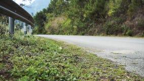 Vrouw die op de wegkant van een landelijke weg lopen stock videobeelden