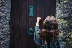 Vrouw die op deur kloppen stock afbeeldingen