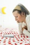 Vrouw die op digitale tablet op haar bed kijken Stock Afbeeldingen