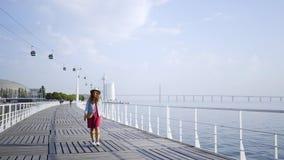 Vrouw die op dijk dichtbij water loopt stock footage