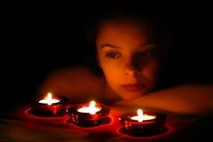 Vrouw die op drie kaarsen kijkt Royalty-vrije Stock Fotografie