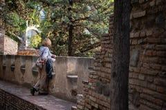 Vrouw die op een balkon leunen die pijnboombomen onder ogen zien stock foto