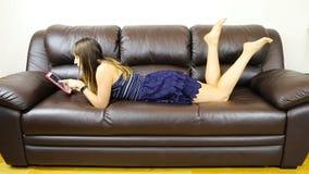 Vrouw die op een bank liggen die pret met een tablet hebben stock footage
